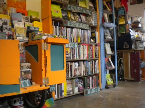 A bike outfitted with a zine bookshelf squeezes into Microcosms new store space.