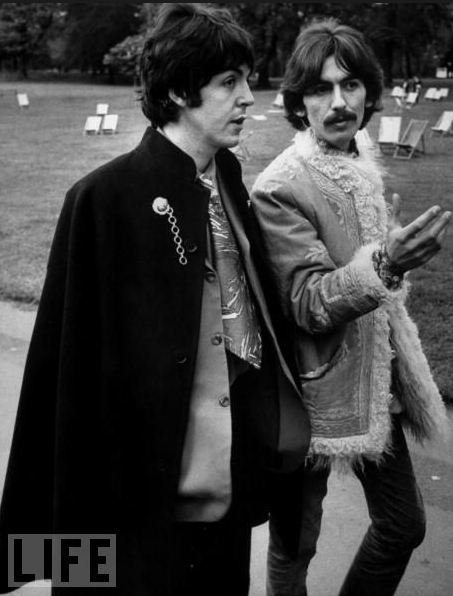 Paul-McCartney-and-George-Harrison-take-a-stroll-through-the-park-in-___67-dressed-to-the-hilt.-A-caped-Paul-over-a-wide-print-tie-George-comfortably-in-embroidered-shearling-they-embodied-the-magic-of-the-Mystery-To.png