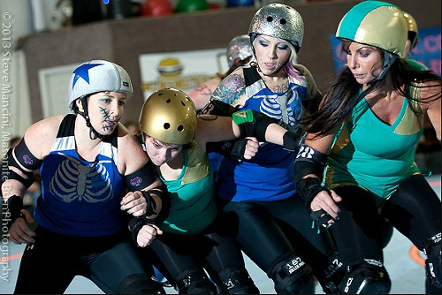 Heartless Heathers jammer Mel Mangles aims to sneak by a complex High Rollers sandwiching of her teammate Tatty Munster.