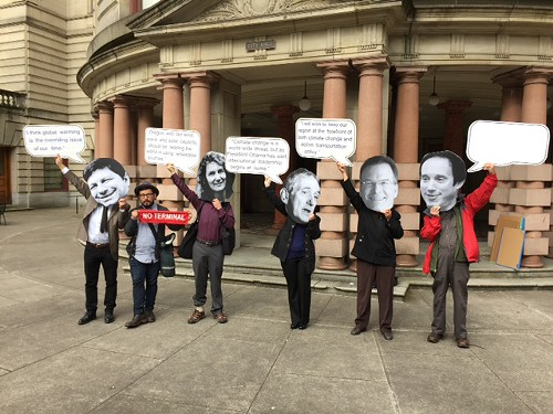 Disembodied heads of Portland commissioners protesting climate change at City Hall. (Photo courtesy of Nick Caleb)